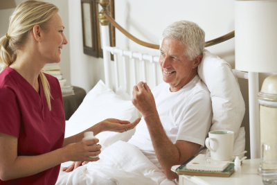 Health Visitor Giving Senior Male Medication In Bed At Home